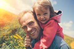Padre joven que juega con su hija linda al aire libre foto de archivo