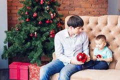 Padre joven que juega con su hijo del bebé en el sofá cerca del árbol de navidad Fotos de archivo libres de regalías