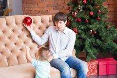Padre joven que juega con su hijo del bebé en el sofá cerca del árbol de navidad Fotos de archivo