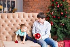 Padre joven que juega con su hijo del bebé en el sofá cerca del árbol de navidad Imagenes de archivo