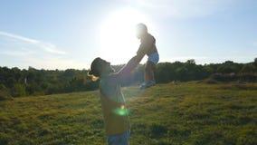 Padre joven que juega con su pequeño hijo al aire libre Papá que levanta encima de su niño en la naturaleza Familia feliz que pas almacen de metraje de vídeo