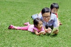 Padre joven que juega con una tablilla digital Imágenes de archivo libres de regalías