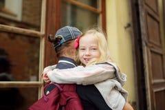 Padre joven que lleva a su pequeña hija adorable durante paseo de la ciudad del verano fotos de archivo