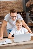 Padre joven que mira a su hijo trabajar en el ordenador portátil Foto de archivo libre de regalías