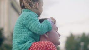 Padre joven que monta a poca hija en hombros mientras que camina en parque del verano metrajes