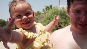 Padre joven que ríe con su pequeña hija al aire libre Primer del padre feliz que se divierte con un bebé almacen de metraje de vídeo