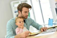 Padre joven que trabaja en el ordenador portátil y que alimenta a su bebé Fotografía de archivo
