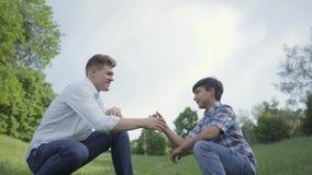 Padre joven y el alto cinco y sacudida del muchacho de las manos al aire libre Padre y un niño que se divierte en el parque perso almacen de video