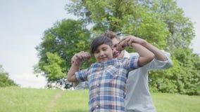 Padre joven y el muchacho que muestra los músculos que miran en la cámara al aire libre Padre y un niño que se divierte en el par almacen de video