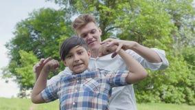 Padre joven y el muchacho que muestra los músculos que miran en el primer del aire libre de la cámara Padre y un niño que se divi almacen de metraje de vídeo