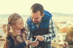 Padre joven y muchacha que miran la guía en teléfono Foto de archivo libre de regalías