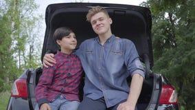 Padre joven y su hijo que se sientan en la parte de atrás del coche al aire libre El hombre que abraza al muchacho, gente que mir almacen de video