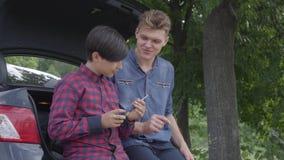 Padre joven y su hijo que se sientan en la parte de atrás del coche al aire libre El muchacho que comprueba el destornillador, el almacen de metraje de vídeo