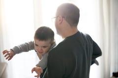 Padre joven y su niño delante de la ventana Foto de archivo