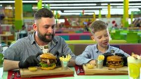Padre joven y su pequeño hijo que comen las hamburguesas en el restaurante metrajes