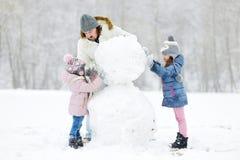 Padre joven y sus hijas que construyen un muñeco de nieve foto de archivo libre de regalías