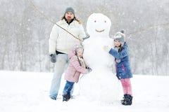 Padre joven y sus hijas que construyen un muñeco de nieve foto de archivo