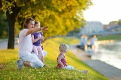Padre joven y sus hijas que se sientan por un río fotos de archivo