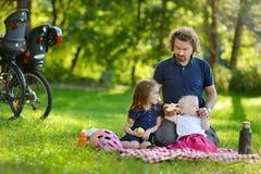 Padre joven y sus hijas que tienen una comida campestre Imagen de archivo