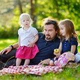 Padre joven y sus hijas que tienen una comida campestre Fotos de archivo libres de regalías