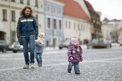 Padre joven y sus muchachas el día de invierno fotos de archivo