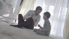 Padre juguetón de la barba que se sienta con su hijo en la alfombra y que sostiene el dinero El papá y el niño pusieron un finger almacen de metraje de vídeo
