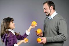 Padre juguetón e hija que juegan con las naranjas Imagenes de archivo