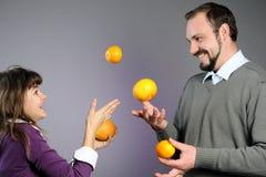 Padre juguetón e hija que juegan con las naranjas Fotos de archivo