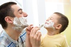 Padre juguetón y su hijo que afeitan en cuarto de baño Imágenes de archivo libres de regalías