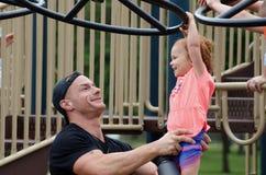 Padre Lifting Daughter sobre el equipo del patio en un parque imágenes de archivo libres de regalías