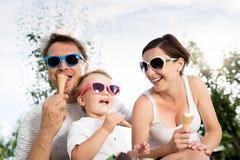 Padre, madre e figlio mangianti il gelato, estate soleggiata Immagine Stock