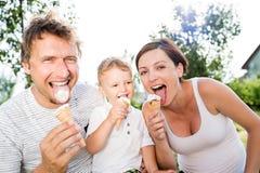 Padre, madre e figlio mangianti il gelato, estate soleggiata Fotografia Stock