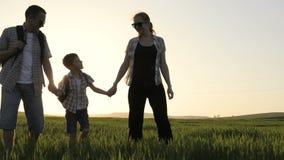 Padre, madre e hijo caminando en el campo en el tiempo de la puesta del sol metrajes