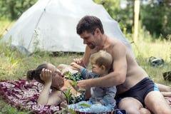 Padre, madre e hijo jovenes 1 3 años que mienten en la hierba una comida campestre El marido da las flores de la esposa Fotos de archivo