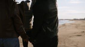 Padre, madre e hijo jugando al aire libre en la playa vacía de la primavera Gente que se divierte en la playa, deteniendo al niño almacen de video