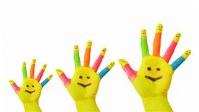 Padre, madre, manos pintadas coloridas del bebé con la cara sonriente Fotos de archivo libres de regalías
