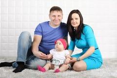 Padre, madre y bebé felices en la alfombra gris. Foto de archivo