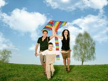 Padre, madre y niño en hierba con la cometa Imagen de archivo libre de regalías