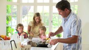 Padre Making Scrambled Eggs para el desayuno de la familia en cocina almacen de video