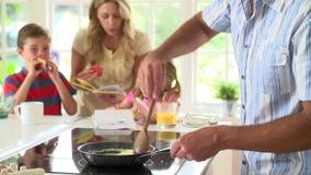 Padre Making Scrambled Eggs para el desayuno de la familia en cocina almacen de metraje de vídeo