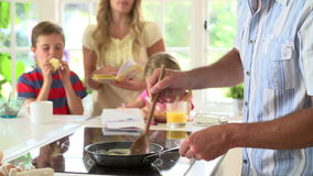 Padre Making Scrambled Eggs per la prima colazione della famiglia in cucina video d archivio
