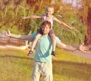 Padre Man de la familia y muchacho del hijo que se sienta en jugar de los hombros al aire libre Foto de archivo