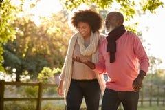 Padre mayor With Adult Daughter que goza de Autumn Walk In Countryside Together fotos de archivo libres de regalías