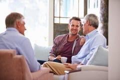 Padre mayor With Adult Son que se relaja en Sofa At Home Imágenes de archivo libres de regalías