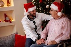 Padre mayor con su día de fiesta sonriente de la Navidad del gasto del hijo foto de archivo libre de regalías