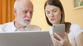 Padre mayor e hija joven que usa smartphone Abuelo de enseñanza adolescente cómo utilizar el teléfono móvil almacen de video