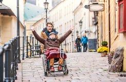 Padre mayor en silla de ruedas e hijo joven en un paseo foto de archivo