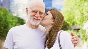 Padre mayor y su hija joven que se colocan en la calle Familia feliz que disfruta del tiempo junto almacen de metraje de vídeo