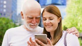 Padre mayor y su hija joven que se colocan en la calle usando smartphone Familia feliz junto metrajes