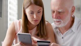 Padre mayor y su hija joven que usa smartphone en casa El hacer compras con la tarjeta de crédito en el teléfono móvil almacen de metraje de vídeo